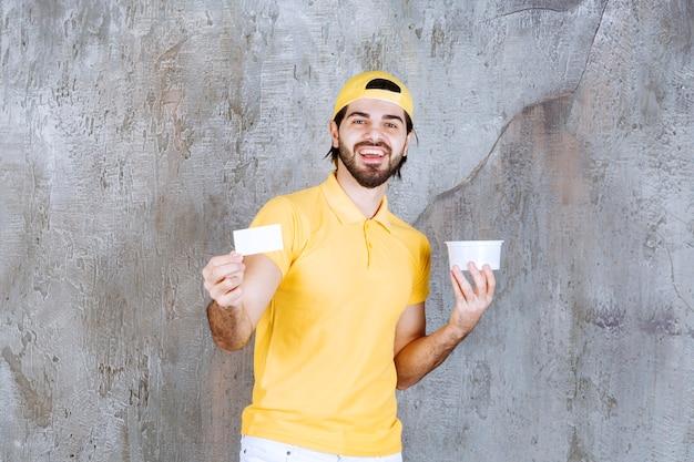 Курьер в желтой форме держит пластиковый стаканчик и представляет свою визитную карточку
