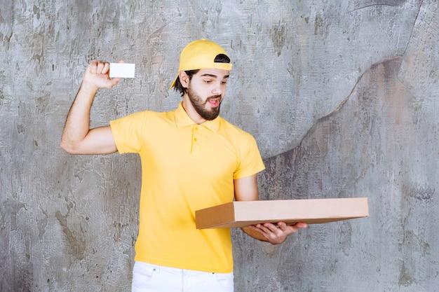 Курьер в желтой форме держит коробку пиццы на вынос и представляет свою визитную карточку.