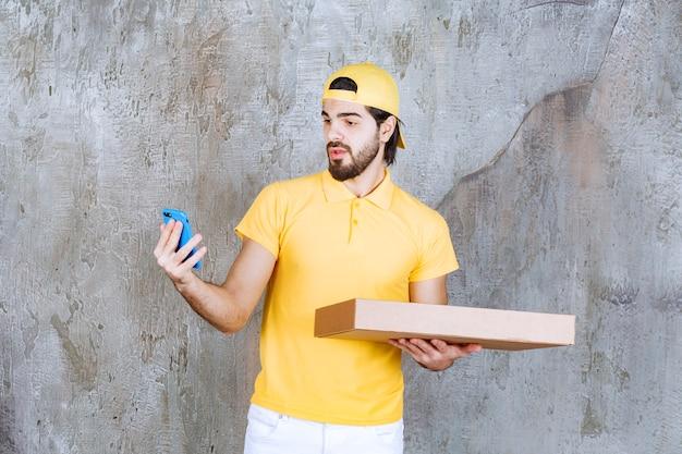 Курьер в желтой форме держит коробку пиццы на вынос и разговаривает по телефону или делает видеозвонок