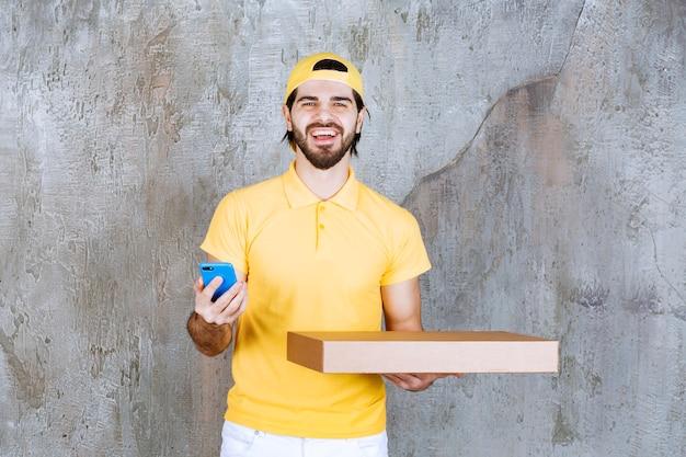 Курьер в желтой форме держит коробку пиццы на вынос и разговаривает по телефону или делает видеозвонок.
