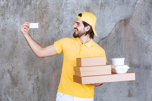 Курьер в желтой форме держит посылки на вынос и картонные коробки и представляет свою визитную карточку.