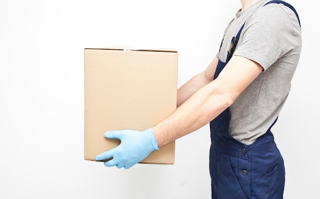 The courier is holding the carton box in his hand wearing  protective latex gloves on the gray wall