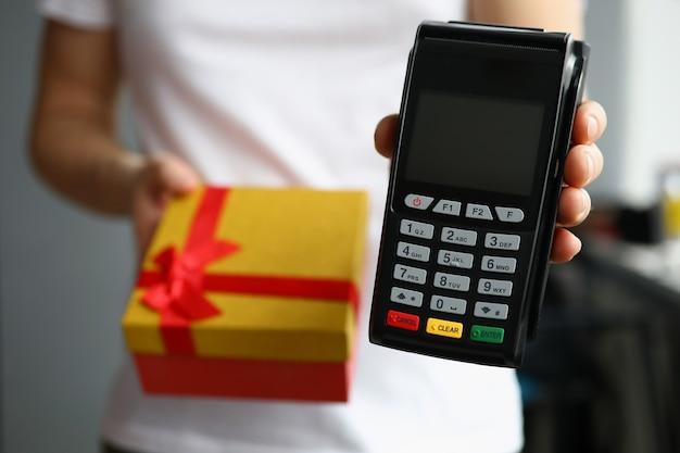 Курьер держит подарочную коробку и платежный терминал