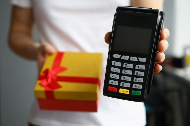 Courier is holding gift box and payment terminal