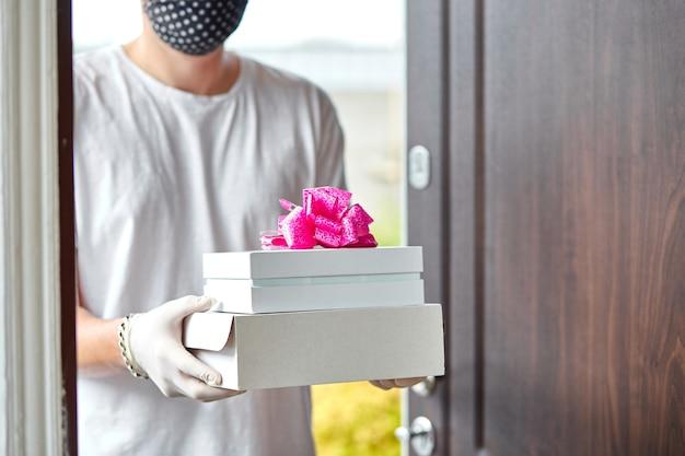 택배 남자 비접촉 배달 선물, 코로나 바이러스 전염병 동안 선물 상자.