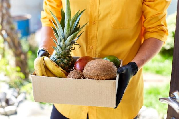 Коробка курьерской доставки с экзотическими фруктами, бесконтактная доставка.
