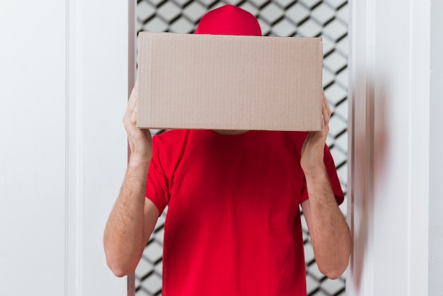 Courier man hiding his face with box