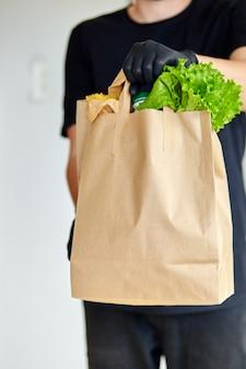 Курьер человек в черном поле доставки с едой, бесконтактная доставка.