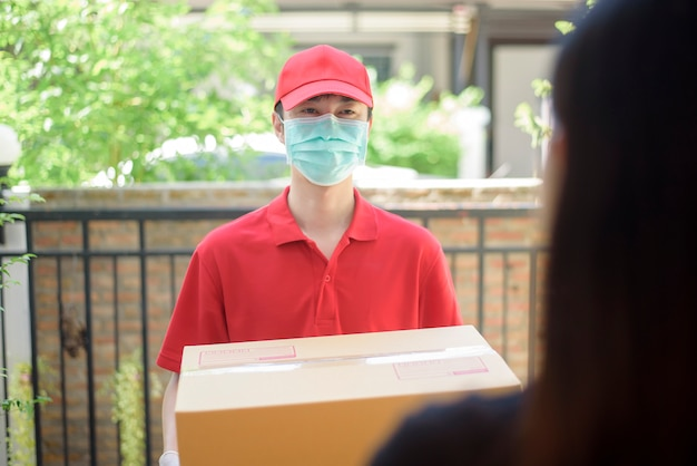 The courier man in protective mask and gloves is deliver box food during virus outbreak. safe home delivery.