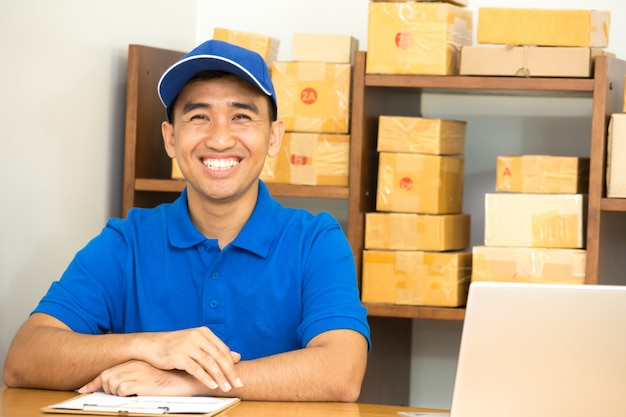 Courier man sitting and smiling with box delivery package at post service warehouse