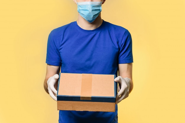 A courier in a medical mask and protective gloves holds a parcel, standing isolated on a yellow wall with place for text.