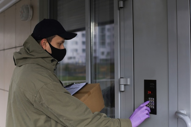 Courier in medicine mask and gloves with parcel calls the intercom to deliver the order to the customer. coronavirus and quarattine concept.