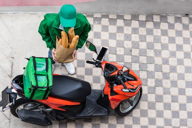 Courier near motorbike wait to deliver bread