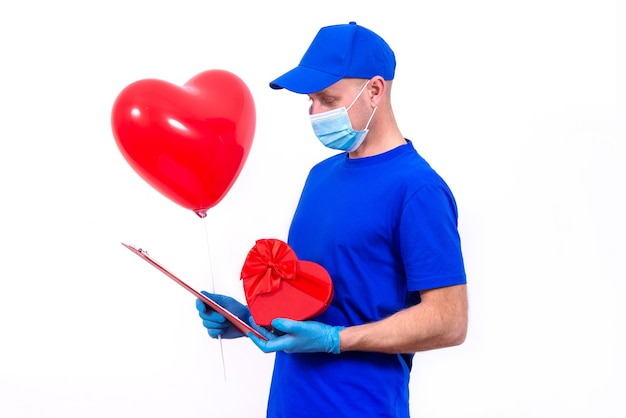 Courier in protective mask, gloves holds red heart-shaped gift box and balloon for valentine's day