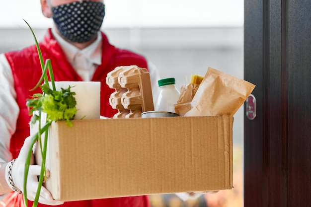 Courier in protective mask and medical gloves delivers food box.