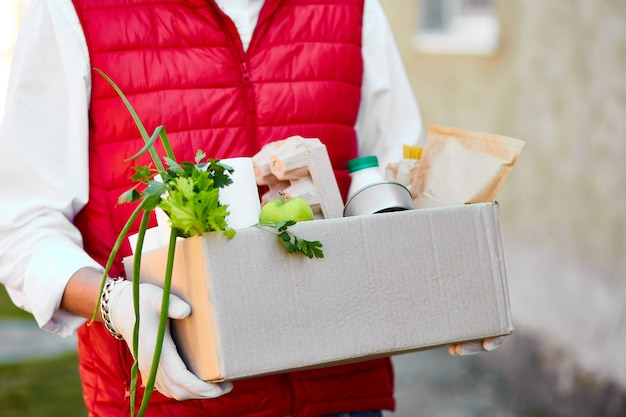 Courier in protective mask and medical gloves delivers food box