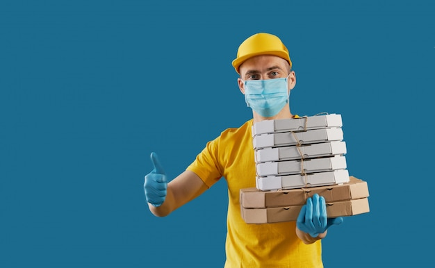 Courier in protective mask and medical gloves delivers takeaway food and coffee. delivery service under quarantine. copy space for text