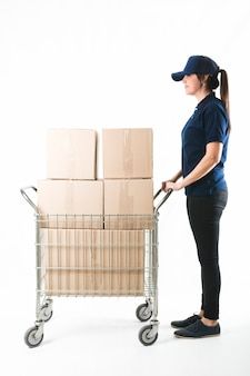 Courier pushing hand truck with stack of boxes