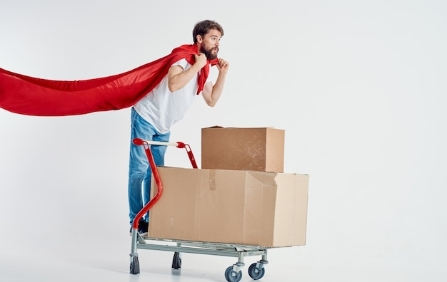 Courier in red cloak superhero cardboard boxes and cargo trolley