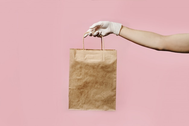 A courier's hand in a protective glove holds a craft package isolated on a pink wall.