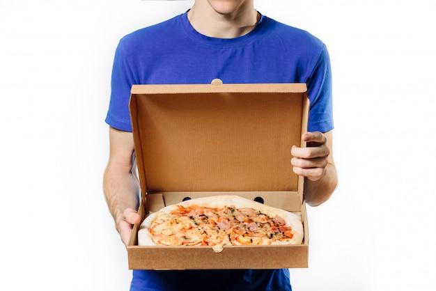 Курьер, стоя на белом фоне, держит картонную коробку с пиццей.