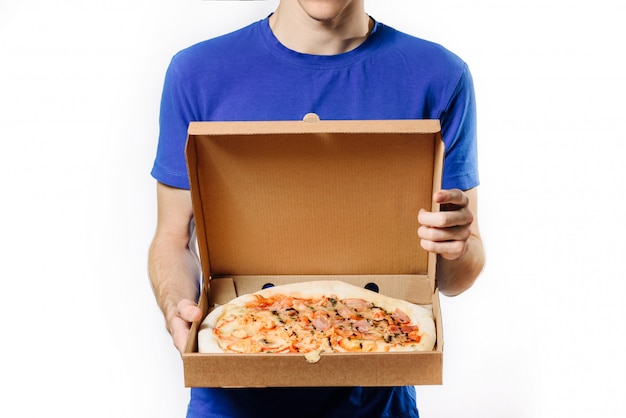 Courier, standing on a white background, holds a cardboard box with pizza.
