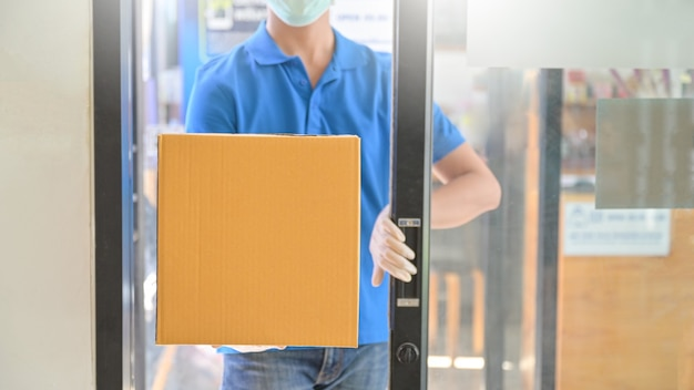 Курьер в маске и резиновой перчатке открывает дверь офиса, чтобы доставить посылки.