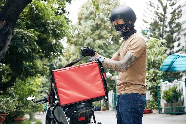 Курьер в бандане и мотоциклетном шлеме прикрепляет изолирующую сумку для доставки еды к мотоциклу ...