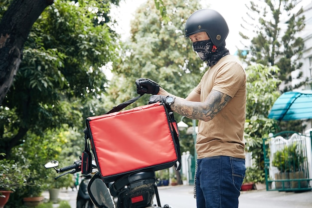 Courier wearing bandana and motorcycling helmet attaching insulated food delivery bag to motorcycle ...
