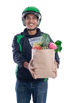 Курьер в шлеме и куртке, держащей еду на белом фоне