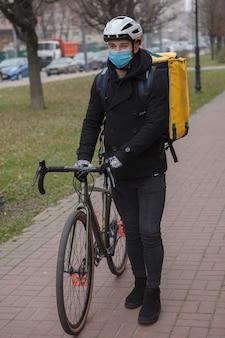 의료용 안면 마스크와 열 전달 배낭을 착용 한 택배, 자전거와 함께 걷기