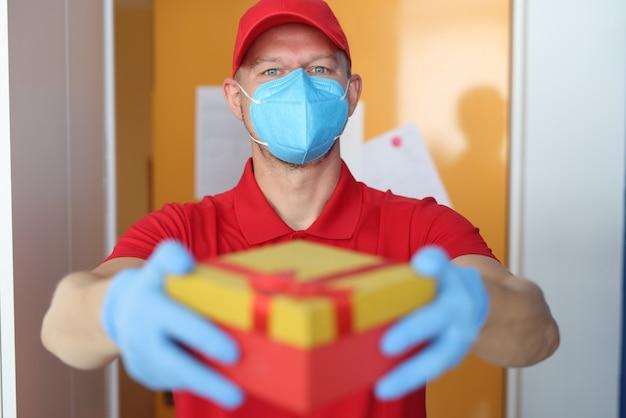 医療用保護マスクを着用した宅配便は、保護手袋付きの箱を持ってきました
