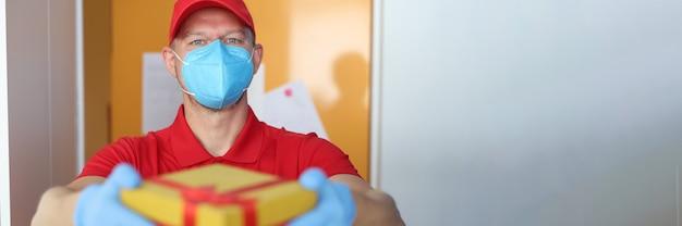 의료용 보호 마스크를 쓴 택배는 보호 장갑이 든 상자를 가져왔다