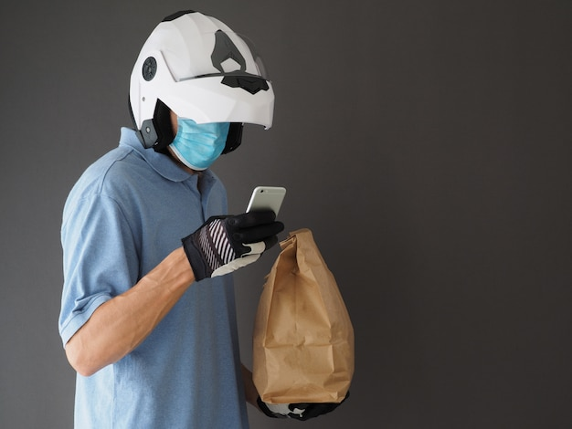 Courier wearing white helmet and protective mask holding food bag and smartphone. concept food delivery during coronavirus pandemic.