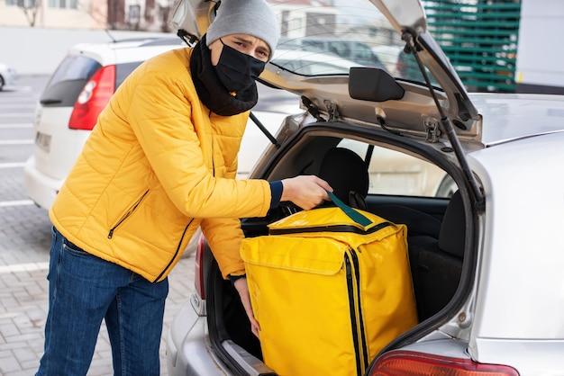 車から黄色のバックパックを取り出す黒い医療マスク付きの宅配便。フードデリバリーサービス