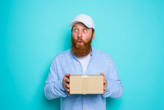 Courier with carton box in hand is surprised about something