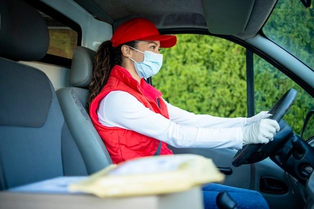 Курьер с маской водит фургон и доставляет посылки во время пандемии коронавируса или covid19