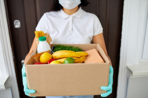 Courier with packing box with food, contactless delivery, service quarantine pandemic coronavirus, volunteer woman in white protective mask and gloves delivery donation box at home.