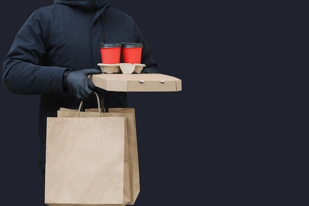 Courier with pizza box, paper bags and coffee cups