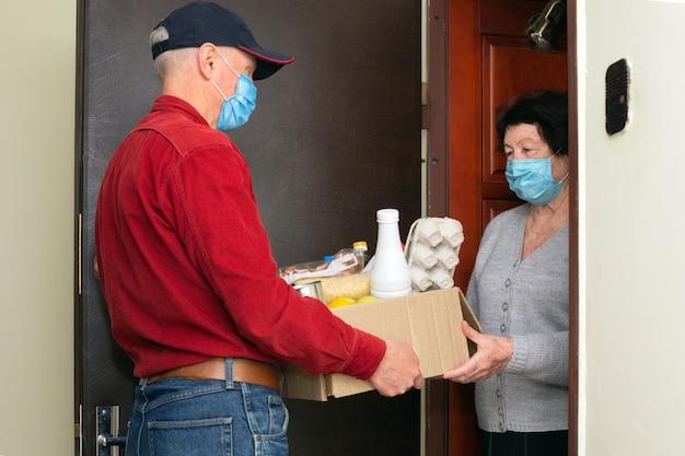 Курьер с защитной маской для лица доставляет покупки пожилой женщине с маской для лица