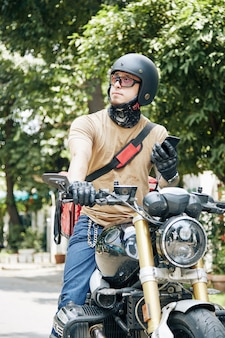 Courier with smartphone in hands sitting on motorcycle and waiting for customer to come down to take...