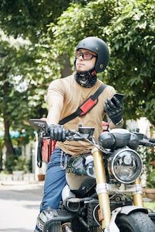 Курьер со смартфоном в руках сидит на мотоцикле и ждет, пока покупатель приедет за ...