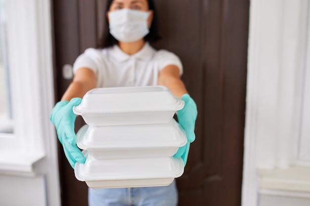 택배 여성 홀드 고 박스 음식, 택배 서비스, 테이크 아웃 식당 음식 집으로 배달, 코로나 바이러스 covid-19 발병으로 집에서 안전하게 생활, 격리 배달 서비스.