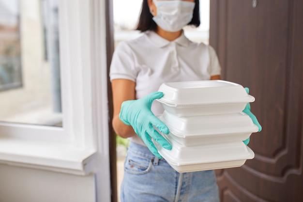 Курьерская женщина держит коробку с едой, служба доставки, доставка еды в ресторанах на вынос до двери дома, оставайтесь дома в безопасности от вспышки коронавируса covid-19, служба доставки в карантине.