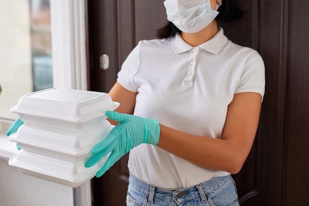 Курьер женщина держит go box food, служба доставки