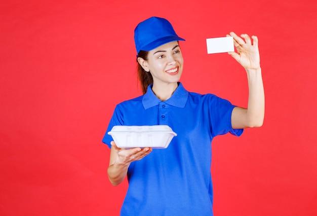白い持ち帰り用の箱を持って名刺を提示する宅配便の女性。