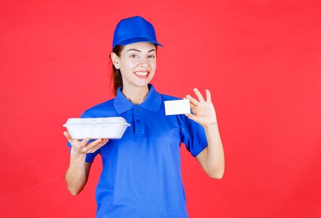 Corriere donna che tiene una scatola bianca da asporto e presenta il suo biglietto da visita.