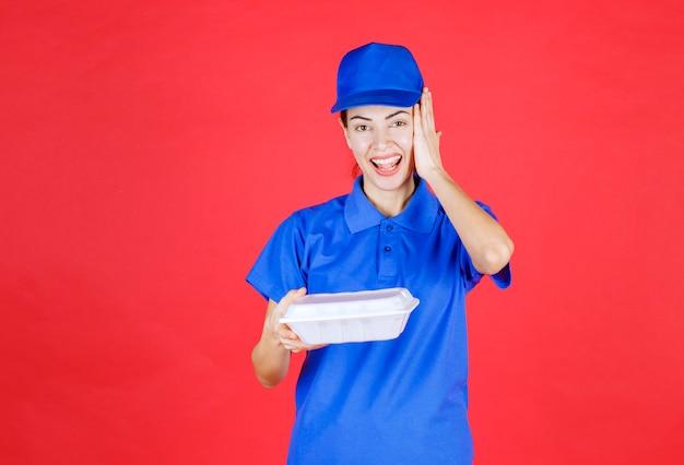 Курьер женщина в синей форме держит белую коробку на вынос и выглядит смущенной и удивленной.