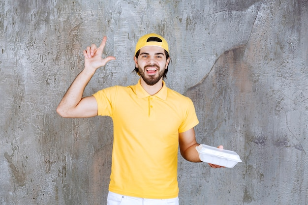 Courier in yellow uniform delivering a plastic takeaway box and looks confused and thinking