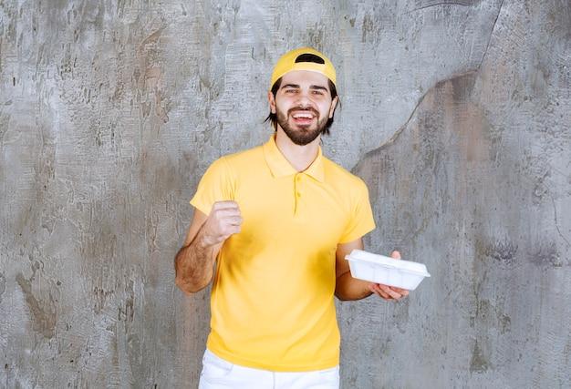 Corriere in uniforme gialla che consegna una scatola di plastica da asporto e mostra un segno positivo con la mano